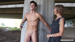 Nympho granny sucks a big cock of tied up naked guy